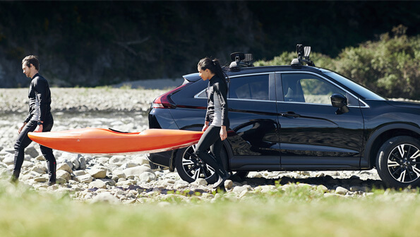 Mitsubishi Eclipse Cross couple with kayaks by a river